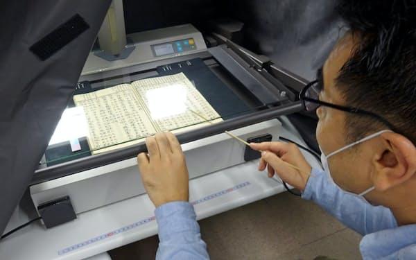 古典籍のデジタル化のため撮影する国文学研究資料館の職員
