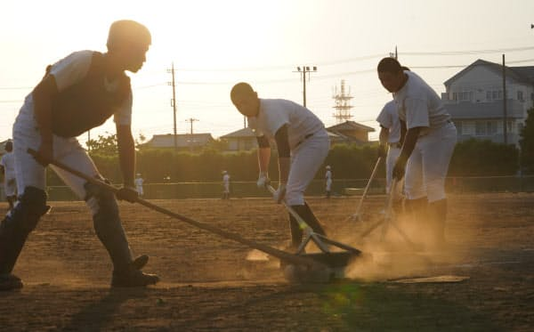 グラウンドを整備する茨城県立石岡第一高校野球部員ら(16日、茨城県石岡市)