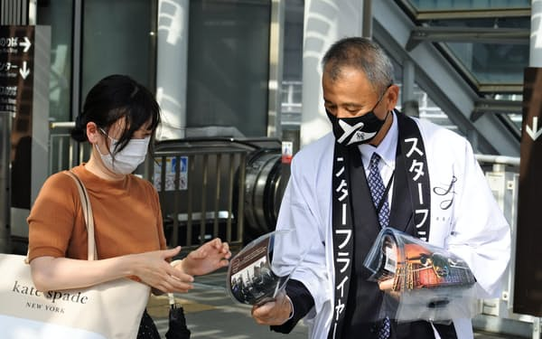 就任初日にJR小倉駅前でビラを配るスターフライヤーの白水社長(右、25日、北九州市)