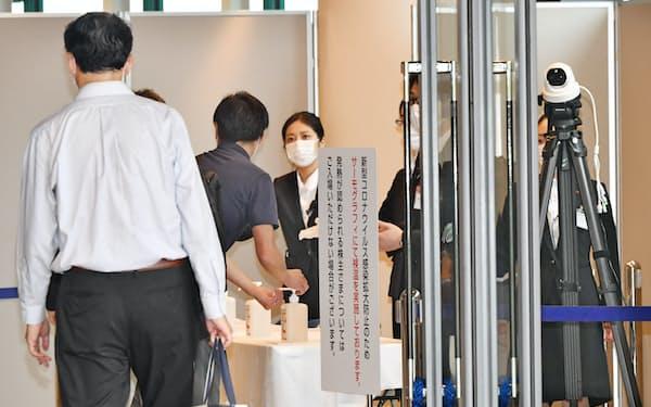 関西電力の株主総会会場に向かう株主ら。入り口にはサーモグラフィーカメラが設置された(25日午前、大阪市住之江区)