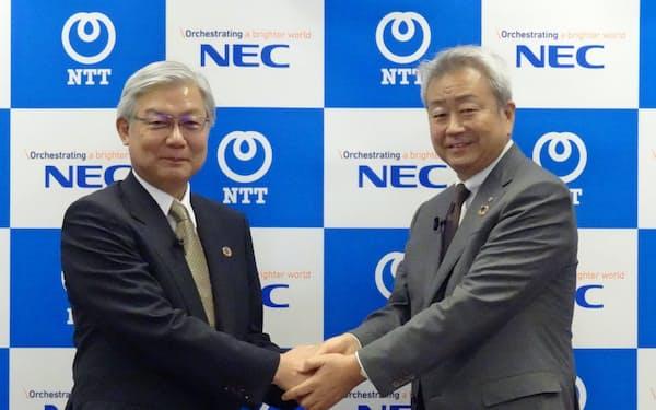 記者会見で握手するNECの新野隆社長(左)とNTTの澤田純社長(25日)