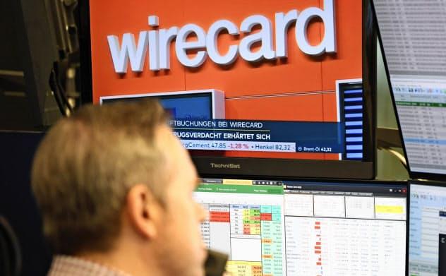 ワイヤーカードについてのニュースが流れるドイツのテレビ画面(22日、フランクフルト証券取引所)=AP