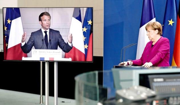 テレビ電話でマクロン仏大統領と復興基金について会談するメルケル独首相(右)=ロイター