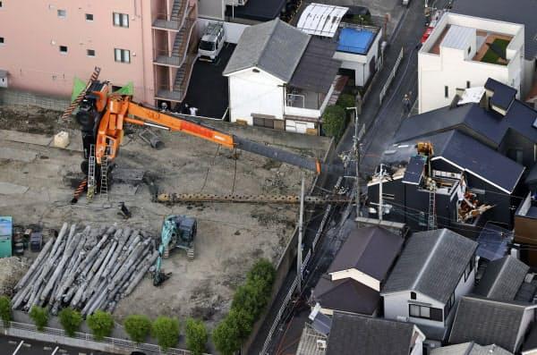 工事現場で倒れて住宅に突っ込んだクレーン車のアーム=26日午後6時3分、大阪府高槻市(共同通信社ヘリから)