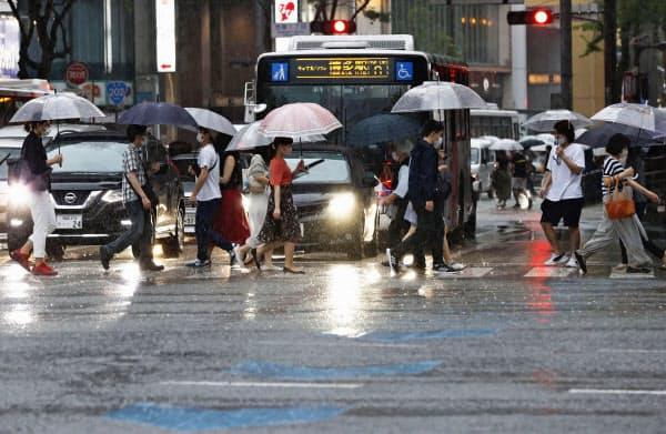 雨の降る福岡・天神を、傘を差して行き交う人たち(27日夕)=共同