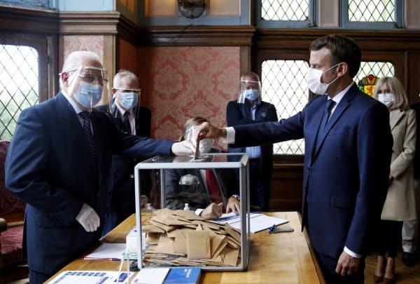 28日、統一地方選で投票するマクロン仏大統領(右)(仏北部)=ロイター
