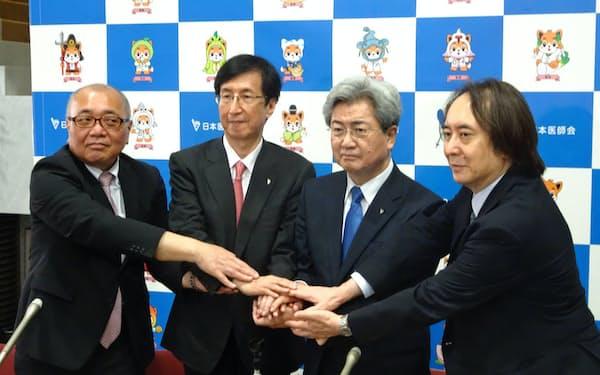 3人の副会長と手を組む中川俊男会長(右から2人目)=6月27日、東京・文京
