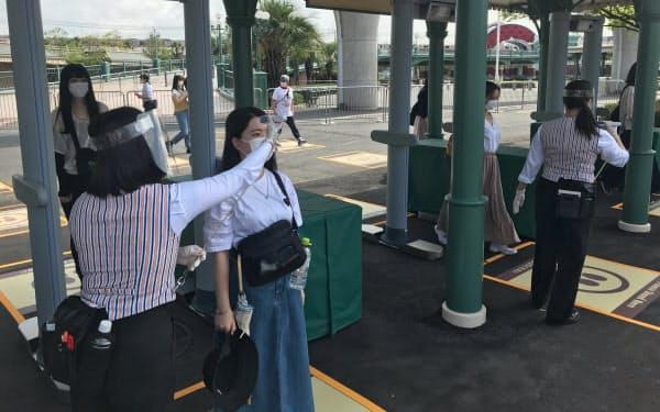 東京ディズニーランドの入り口では来園者に検温を実施する。