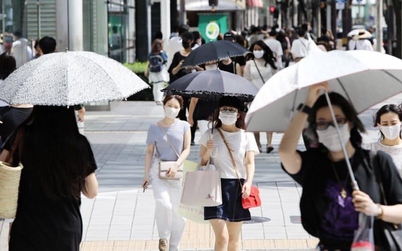強い日差しの下、日傘を差して歩く人たち(29日、名古屋市中区)