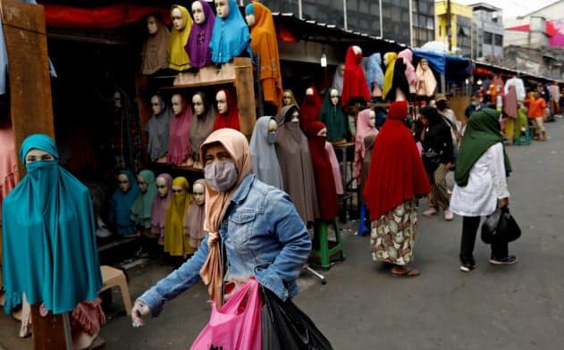 マーケットでマスクをして買い物する女性(4月、ジャカルタ)=ロイター