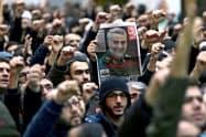 ソレイマニ氏の写真を掲げ米国を批判するデモ参加者(1月4日、イラン首都テヘラン)=ロイター