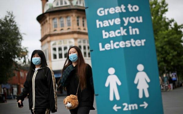 マスク姿で街を行く人たち(29日、英中部レスター)=ロイター