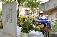 米軍機墜落事故の犠牲者18人の名前を刻んだ石碑「仲よし地蔵」に花と千羽鶴を供える児童(30日午前、沖縄県うるま市の宮森小)=共同