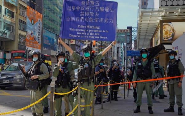 28日、香港の街で警戒に当たる警察官=AP