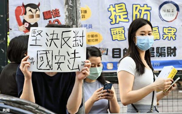 6月28日、デモ行進が行われた香港・九竜地区で「国家安全法に断固反対」と書かれた紙を掲げる人=共同