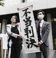 東京地裁が原告の請求を棄却し、掲げられた「不当判決」の垂れ幕(30日、東京地裁前)
