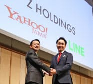 統合発表時の記者会見で握手するZHDの川辺健太郎社長(左)とLINE出沢剛社長(2019年11月)