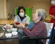 食事の介助を体験する高知大生の紀藤さん(左)(29日、高知市内のケアビレッジあさくら)