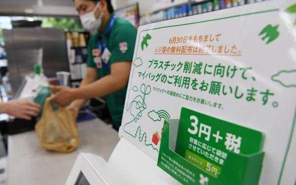 レジ袋の有料化を知らせる案内が掲示されたセブンイレブンの店舗(1日午前、東京都港区)