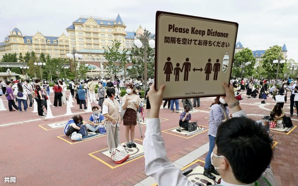 東京ディズニーランドのエントランス前で、距離を空けて開園を待つ人たち(1日午前、千葉県浦安市)=共同