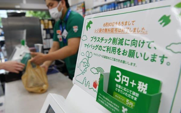 レジ袋の有料化を知らせる案内が掲示されたセブンイレブンの店舗(1日、東京都港区)