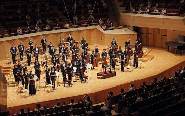 拍手を受ける東京交響楽団の楽団員ら(6月26日、東京都港区のサントリーホール)
