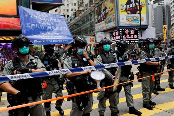 1日、香港の繁華街に並ぶ警察官=ロイター
