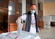 プーチン氏に斜線を引いたイラストのTシャツを着て期日前投票を行った男性(6月30日、モスクワ)=ロイター
