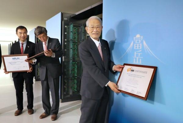 スパコンのランキングで世界一となり、「富岳」の前で記念写真に納まる理研の松本紘理事長(右)=6月23日、神戸市中央区