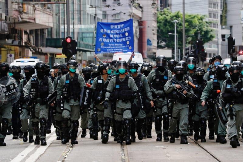 1日、香港でデモ隊を取り締まる警察官=ロイター