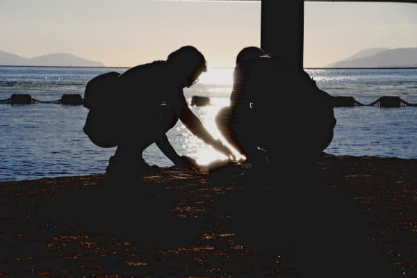 箱崎浜でお汐井とりをする人たち(1日、福岡市東区)