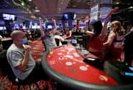 米ラスベガスの営業再開したカジノで接客する従業員(6月4日)=ロイター