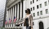 ニューヨーク証券取引所前を歩くマスク姿の女性(6月30日)=AP
