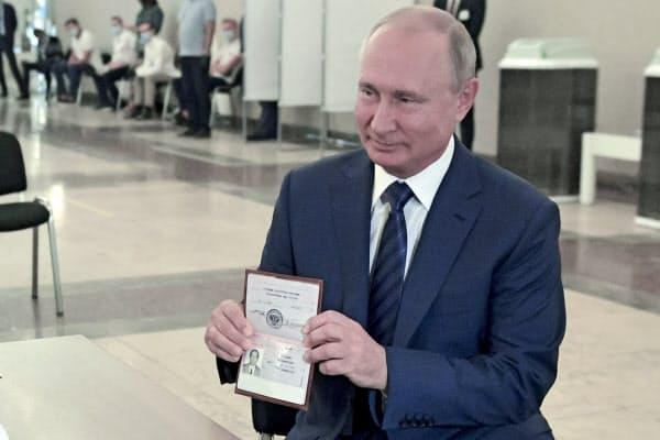 投票用紙を受け取るためにパスポートを提示したプーチン氏(1日、モスクワ)=AP