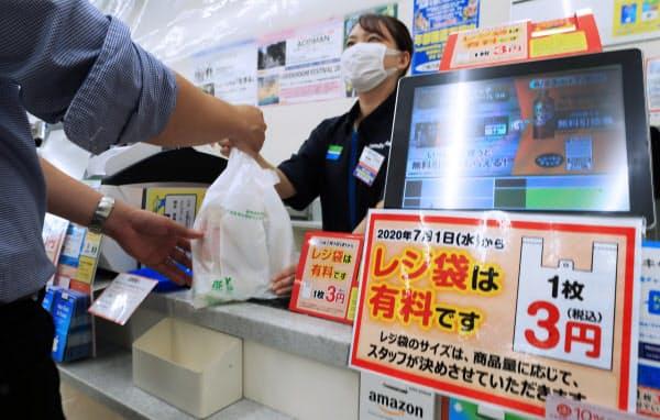 コンビニのレジに出されたレジ袋有料化の案内(1日、東京都中央区のファミリーマートの店舗)