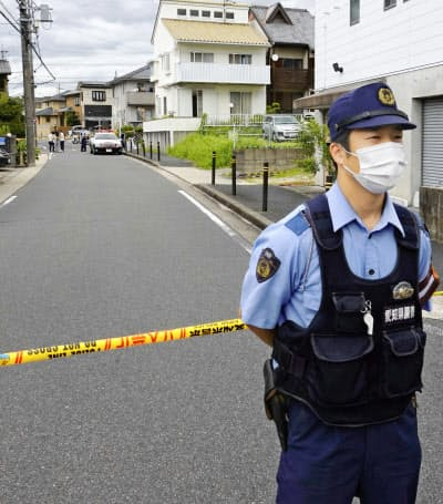 男性が刺された現場(左奥)の付近を警戒する警察官(2日午後、名古屋市名東区)=共同