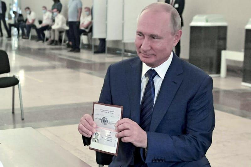 1日、投票所を訪れ、身分証明書を見せるプーチン大統領(AP=共同)