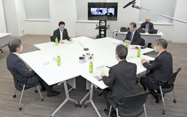 新型コロナウイルス感染症対策の検証会議の初会合であいさつする西村経財相(左上)、その右は黒川清委員長(1日午前)