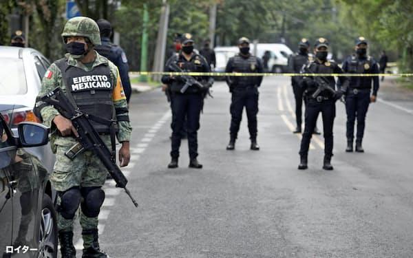 メキシコシティの治安庁長官が襲撃された現場付近を警備する警察ら(6月26日)=ロイター