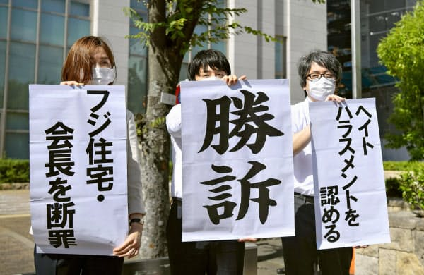 大阪地裁堺支部前で「勝訴」などと書かれた垂れ幕を掲げる原告側の弁護士(2日午後)=共同