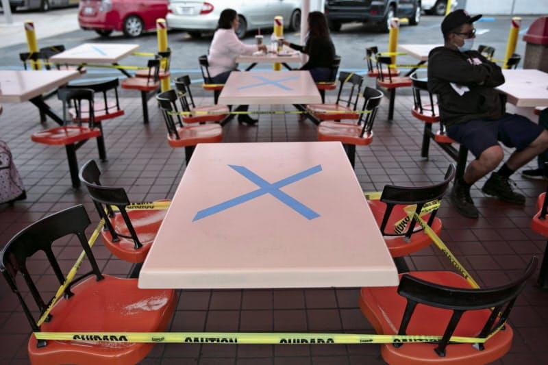 社会的距離を保つため、座れない席に目印をつけるレストランも(1日、ロサンゼルス)=AP