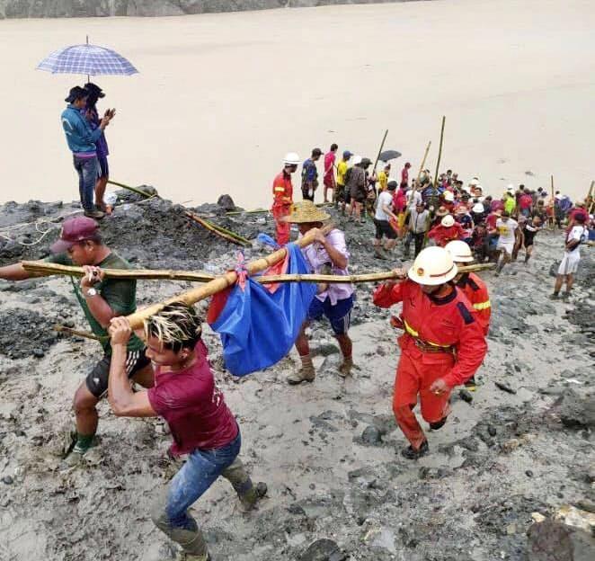 ミャンマー北部カチン州パカンの翡翠鉱山で、土石崩落事故の犠牲者の遺体を運ぶ救急隊員ら(2日)=ミャンマー消防局提供・共同