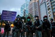 6月、金融機関の高層ビルが立ち並ぶ香港の街で、デモ隊制圧のため出動する警察=ロイター