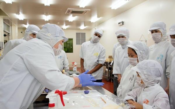 「こども参観」でお菓子づくりの説明を受ける従業員の子どもたち(2019年8月、近江八幡工場)