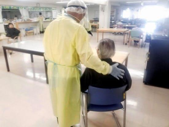 集団感染が起きた札幌市の介護老人保健施設で、入所者(右)に寄り添う防護服姿の介護スタッフ(同施設提供)=共同