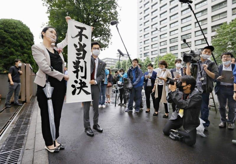 旧優生保護法下での強制不妊手術を巡る訴訟の判決で、請求が棄却され「不当判決」の垂れ幕を掲げる原告側弁護士=30日午後、東京地裁前(共同)