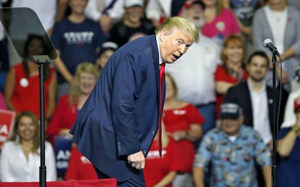 背中を曲げてスロープを下りる姿を再現するトランプ米大統領(6月20日)=ロイター