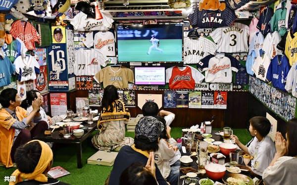 プロ野球公式戦が開幕した6月19日、東京・神田の居酒屋でテレビ観戦するファン。解説と実況がかみ合えばファンもより楽しめるはずだ=共同