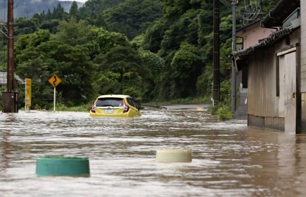 水に漬かった道路で立ち往生する車(4日午前9時38分、熊本県八代市)=共同