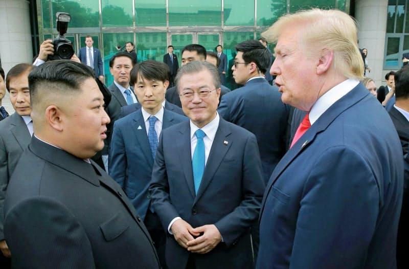 韓国の文在寅大統領(中)は「米朝首脳会談開催に全力を尽くす」と話す(写真は19年6月の首脳会談)=朝鮮中央通信・共同